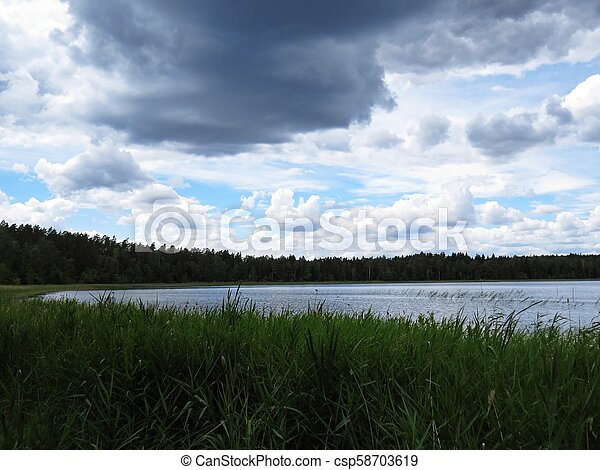 View at Panorama of Tranquil Lake with Trees and Clouds - csp58703619