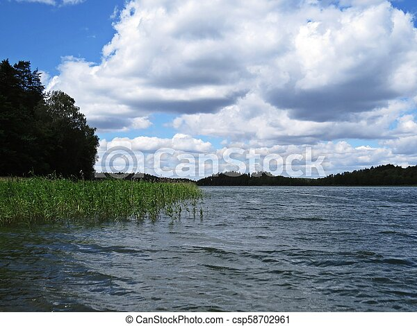 View at Panorama of Tranquil Lake with Trees and Clouds - csp58702961