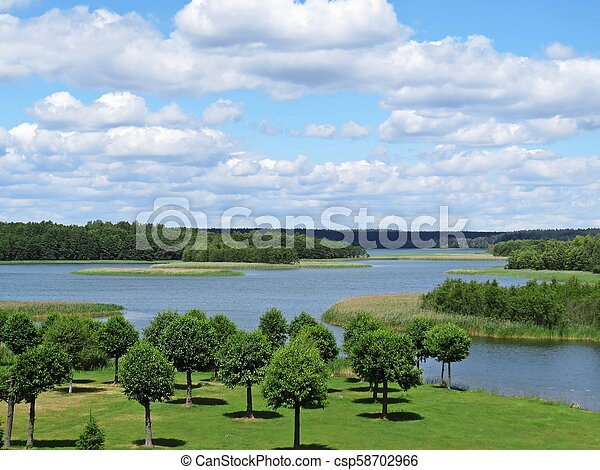 View at Panorama of Tranquil Lake with Trees and Clouds - csp58702966