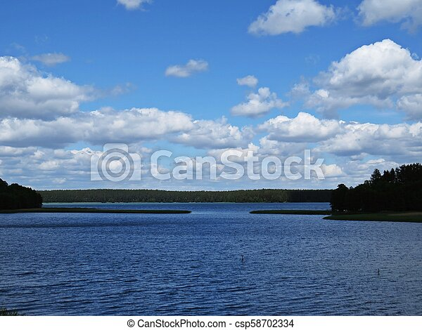 View at Panorama of Tranquil Lake with Trees and Clouds - csp58702334