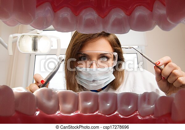 View at young female dentist with dental tools from patient's mouth  - csp17278696