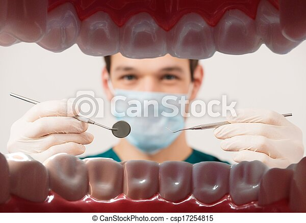 View at young male dentist holding dental tools from patient mouth  - csp17254815