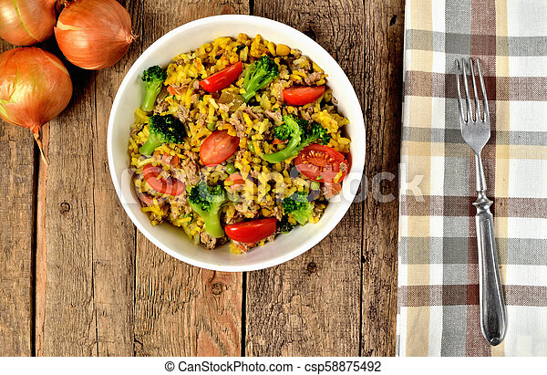 View from above of bowl with tuna risotto with vegetables, tomatoes, broccoli and parsley, onions and brown checkered tablecloth in right frame - csp58875492