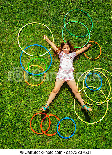 View from above of happy girl on grass with rings - csp73237601