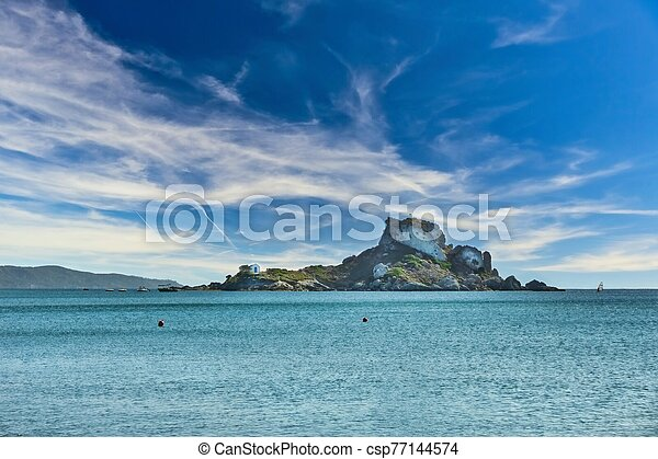 View from beach on Kos island to small rock with church - csp77144574