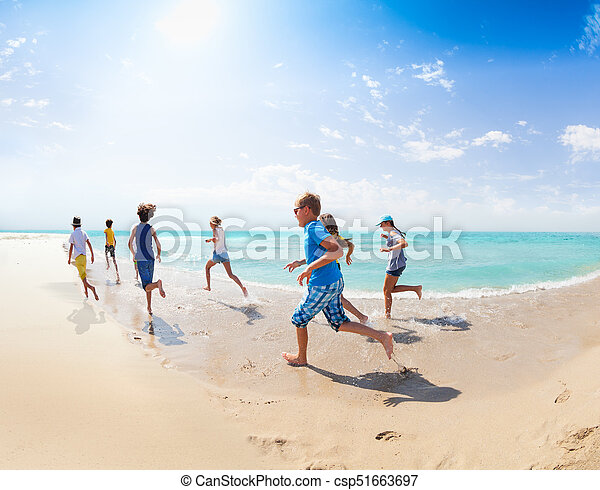 View From Behind Of Kids Run On The Sea Beach Stock Photo