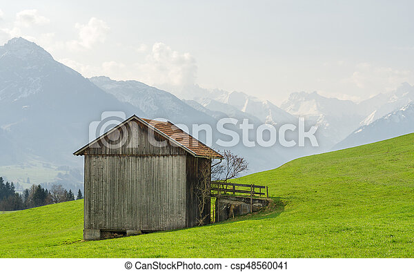 View from wooden barn to snow covered mountains in springtime - csp48560041