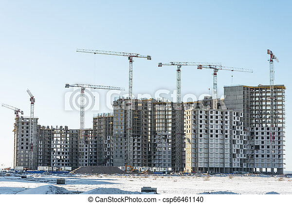 View of a residential complex under construction with high cranes. Large-scale building of the city - csp66461140