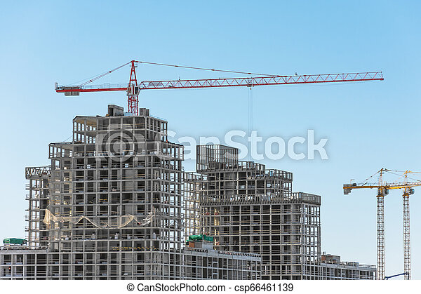 View of a residential complex under construction with high cranes. Large-scale building of the city - csp66461139