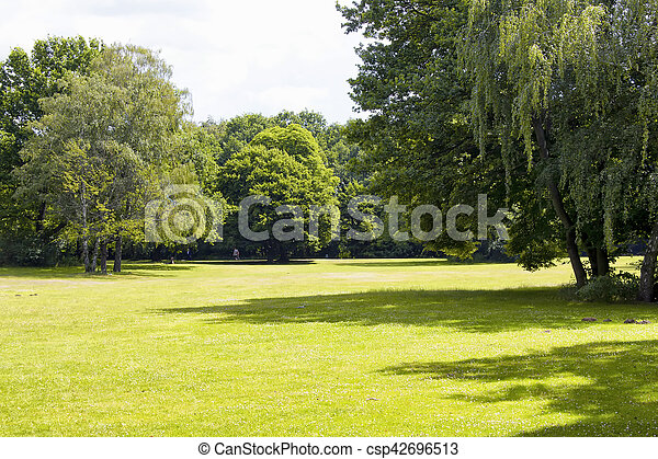 View of grass field and trees at Tiergarten in Berlin. The largest & oldest park, including family amenities, walking paths & a victory column. - csp42696513