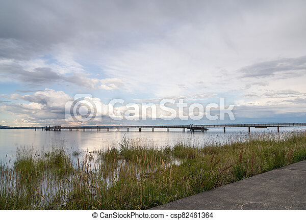 view of Lake Constance with the pier at Altnau in evening light - csp82461364