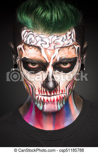 view of man with green hair and halloween makeup mystical face art man with colored dead face skull mask