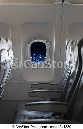 View of modern city skyline at night in an airplane window - csp44241589
