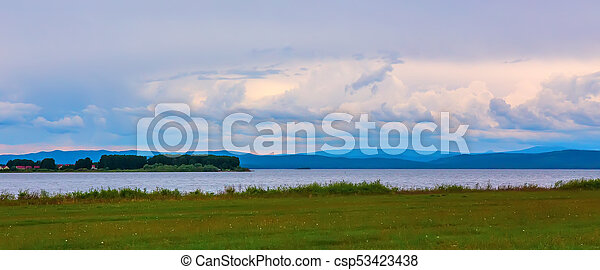 view of the lake with an island and a cloudy sky - csp53423438