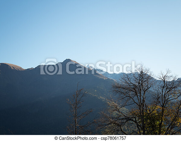 View of the mountain peaks in the backlight against the blue sky - csp78061757
