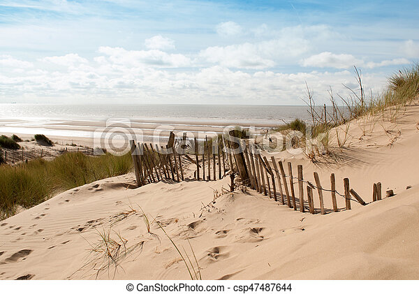 View of the sea from sand dune with old fence - csp47487644