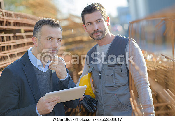 view of two workers working outside on a construction site - csp52502617