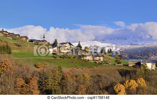 view on alpine village in a hill and snowy mountain background - csp91768148