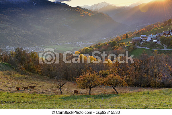 view on pasture with  alpine village in a hill under the sun at sunset - csp92315530