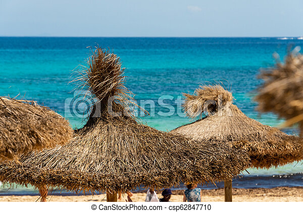 View over straw parasols from the beach Cala Agulla to the turquoise Mediterranean Sea on the Spanish holiday island Mallorca - csp62847710