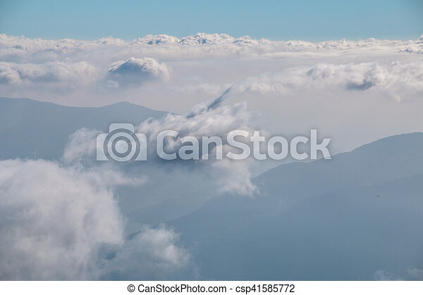View over the clouds in the sky with mountains in the background - csp41585772