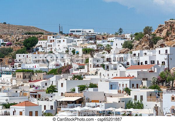 View over whitewash houses with rooftops in Lindos Town from path leading to Acropolis. Greek Island of Rhodes. Europe. - csp65201887