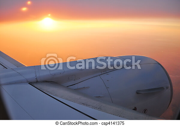 View to sunset sky and sun from the plane with the detail of plane wing and turbines - csp4141375