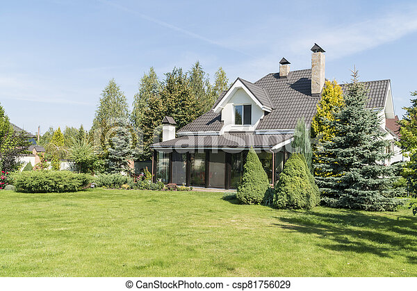 village house with its beautiful garden in a rural area under blue sky - csp81756029