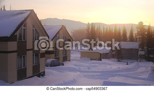 Village in the mountains at amazing sunrise. Fantastic winter landscape. Snowy mountains. - csp54903367