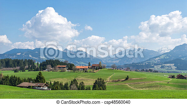 Village surrounded by green forests and snow covered mountains - csp48560040