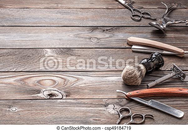 Vintage barber shop tools on wooden background - csp49184719