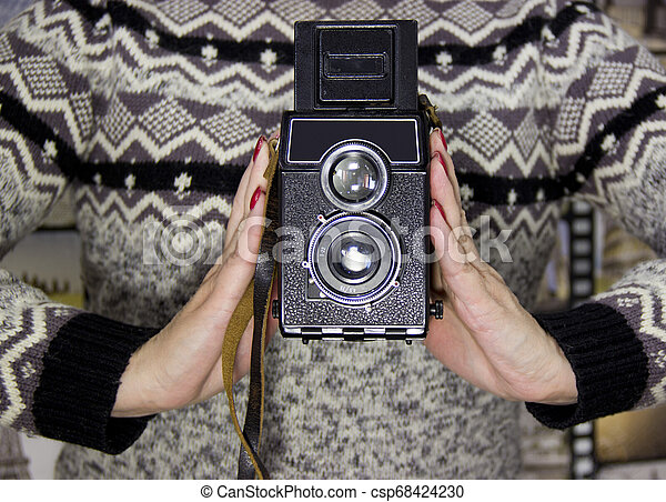 vintage camera in the hands of a girl - csp68424230