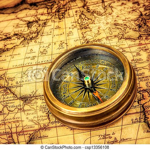 Vintage compass lies on an ancient world map. - csp13356108