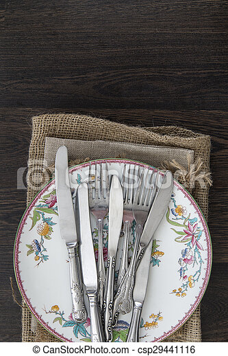 Vintage cutlery and crockery on cloths on rustic wooden background - csp29441116