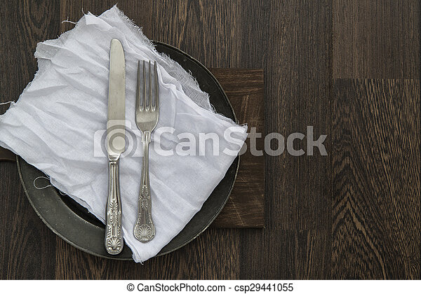 Vintage cutlery on muslin cloth on pewter plate with rustic dark wood backgorund - csp29441055