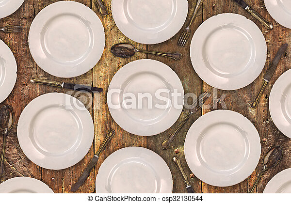 Vintage dinner plates, knives, forks and spoons on an old table - csp32130544