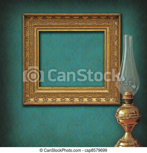 Vintage empty frame on damask wallpaper with antique oil lamp - csp8579699