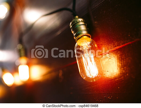 Vintage incandescent Edison type bulbs on wooden wall - csp84619468