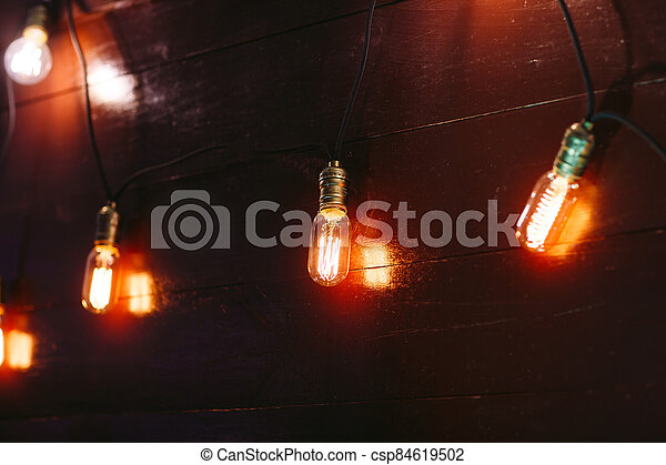 Vintage incandescent Edison type bulbs on wooden wall - csp84619502