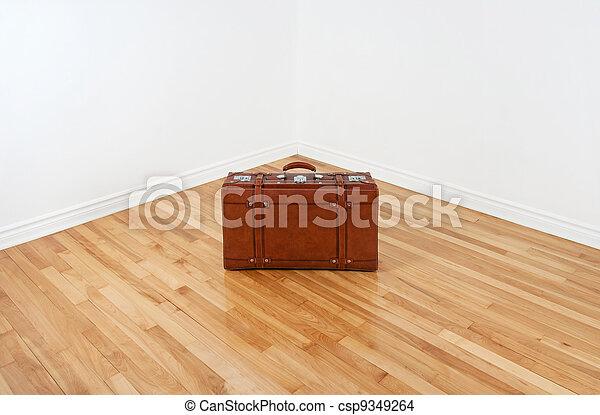 Vintage leather suitcase in empty room corner - csp9349264