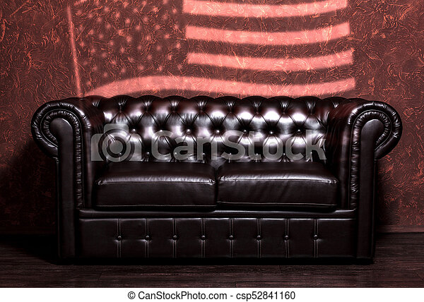 Vintage old dark brown leather sofa with grunge brown wall with the USA  flag in the living room