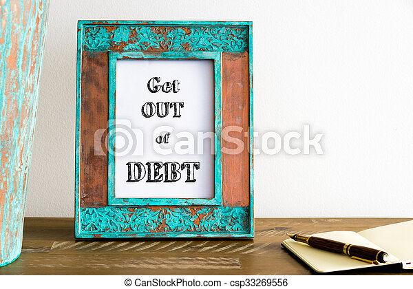 Vintage photo frame on wooden table with text GET OUT OF DEBT - csp33269556