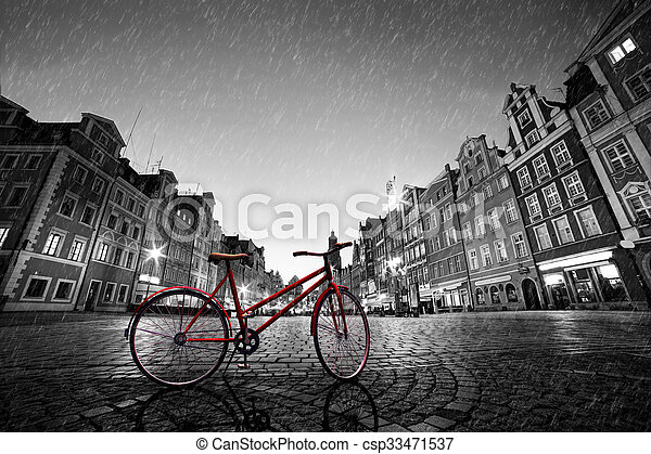 Vintage red bike on cobblestone historic old town in rain. Wroclaw, Poland. - csp33471537