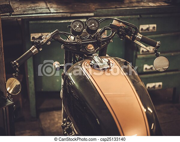 Vintage style cafe-racer motorcycle in customs garage  - csp25133140