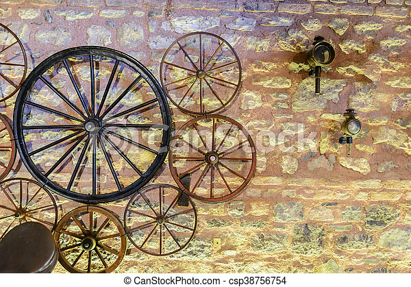 vintage wheels various carts on the background of a stone wall - csp38756754