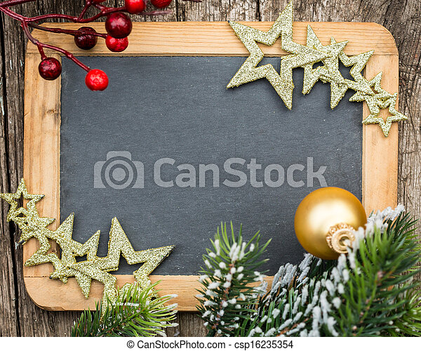 Vintage wooden blackboard blank framed in Christmas tree branch and decorations. Winter holidays concept. Copy space for your text - csp16235354
