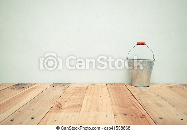 Vintage zinc bucket on wooden table and cement wall background - csp41538868