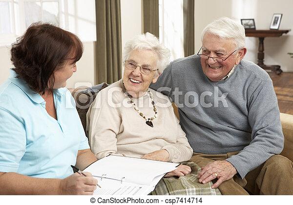 Una pareja mayor en discusión con un visitante de la salud en casa - csp7414714