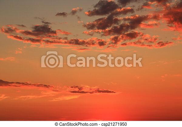 Vivid peach sunset sky with light clouds - csp21271950