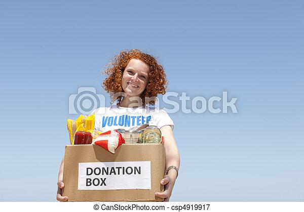 volunteer carrying food donation box - csp4919917